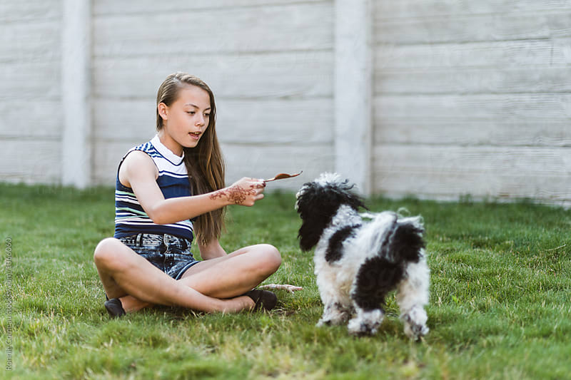 Teen Girl Playing With Her Dog by Ronnie Comeau for Stocksy United
