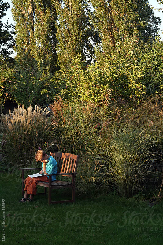 Young boy reading a book in the garden by Marcel for Stocksy United