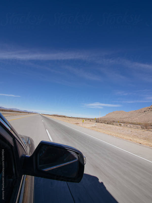 Point of view shot of car traveling down highway in desert setting by Jeremy Pawlowski for Stocksy United
