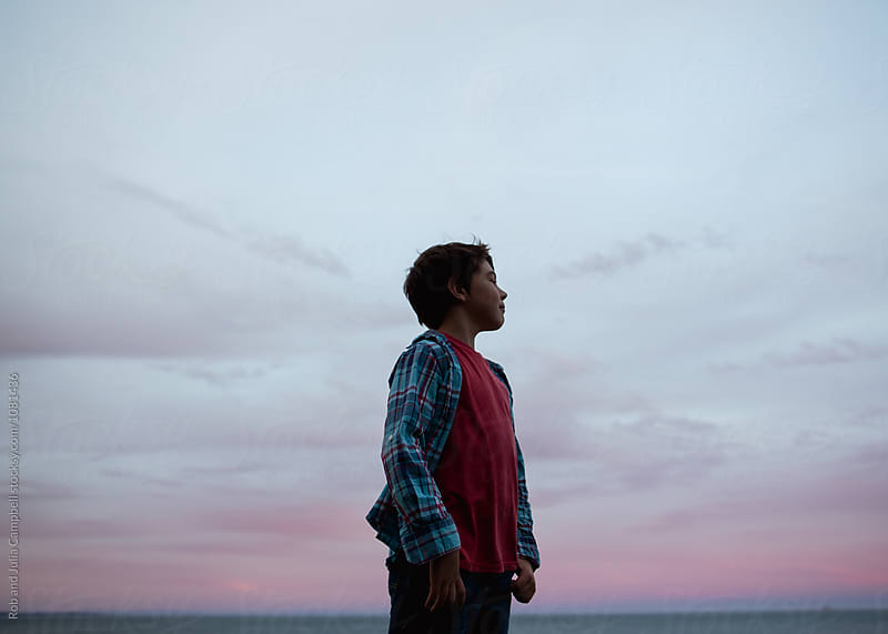 Young preteen caucasian boy outside in nature - looking out at sunset by Rob and Julia Campbell for Stocksy United