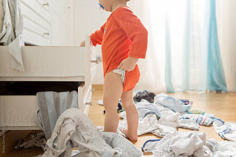 1 year old boy throws out clothes from wooden furniture at home by Nasos Zovoilis for Stocksy United