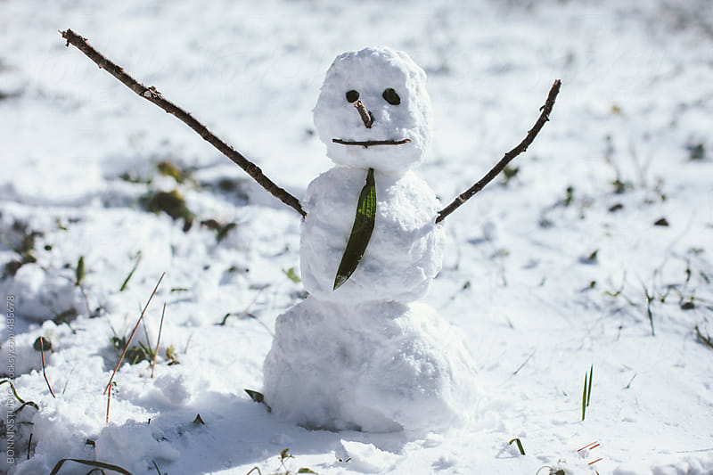 Simple small snowman on snowy grass.  by BONNINSTUDIO for Stocksy United