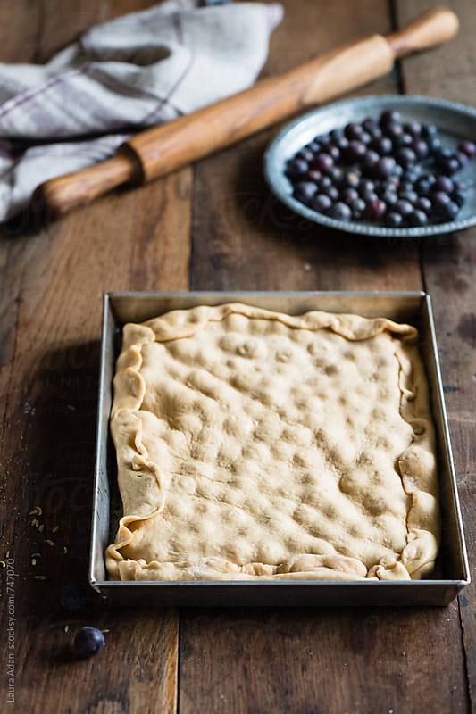 preparing homemade sweet focaccia stuffed with black grape by Laura Adani for Stocksy United