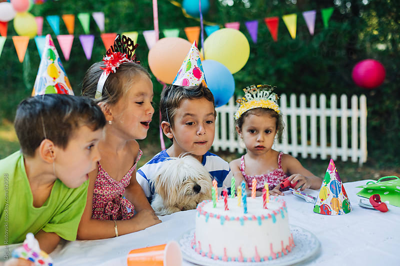 Children celebrating birthday outdoors by Dejan Ristovski for Stocksy United