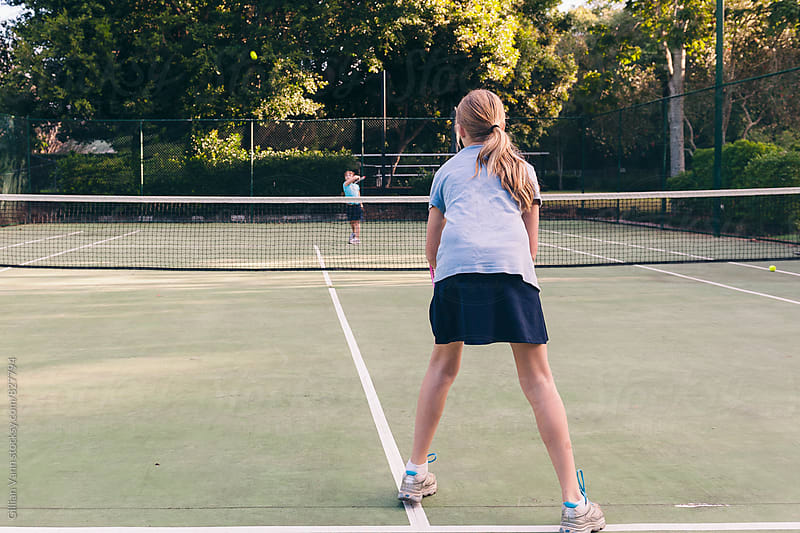 tween girls playing tennis by Gillian Vann for Stocksy United