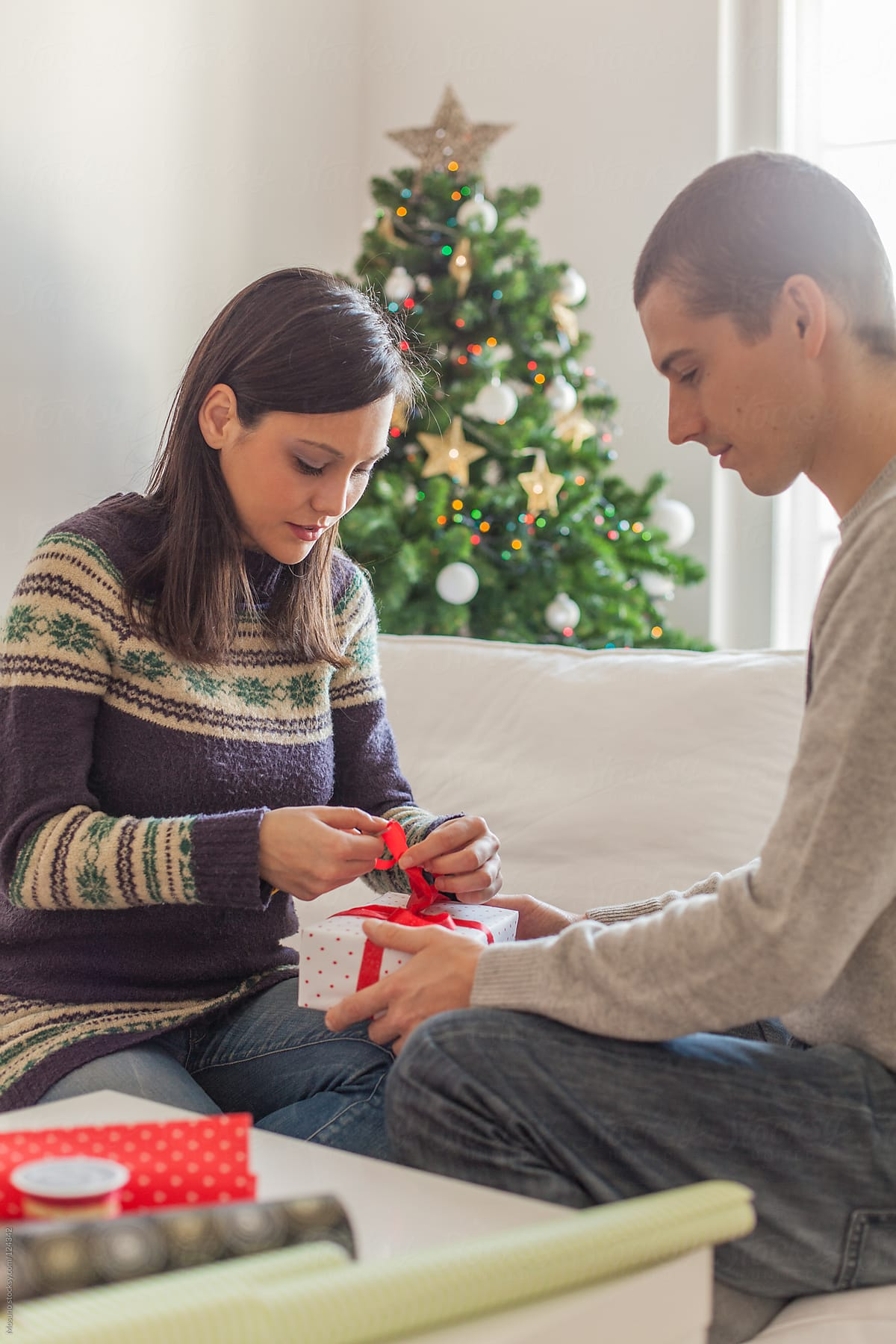 young couple wrapping christmas gifts by mosuno for stocksy united