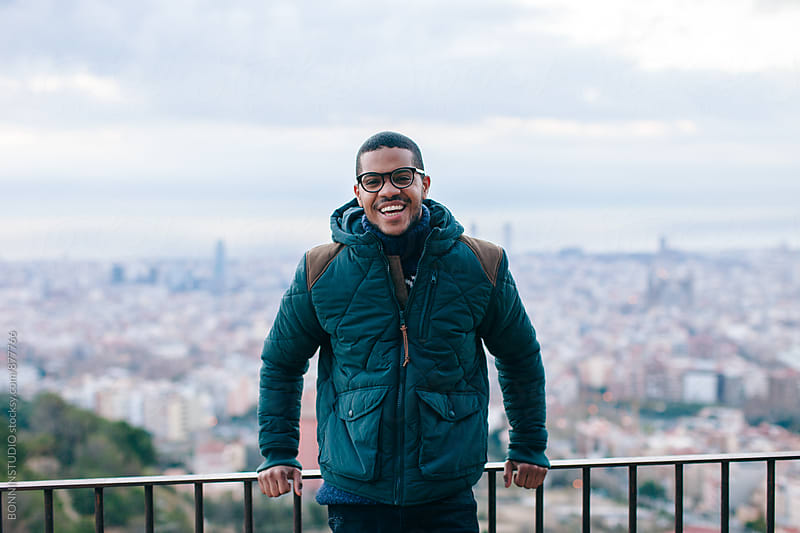 Portrait of a latin man smiling standing above city. by BONNINSTUDIO for Stocksy United