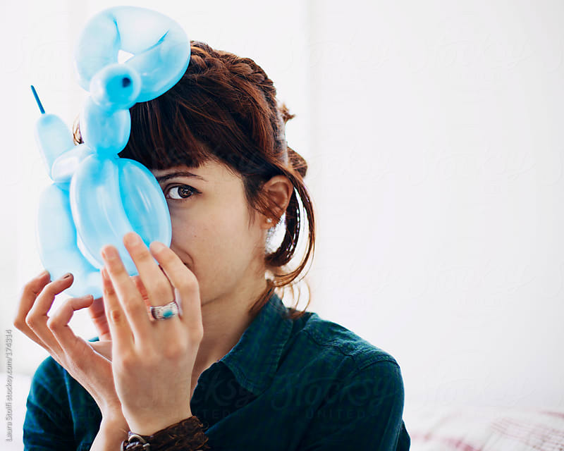 Attractive woman peeks from behind a dog shaped ballon she holds in front of her face by Laura Stolfi for Stocksy United