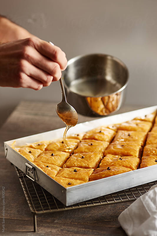 Close-up of man's hand covering hot baklava with honey by Martí Sans for Stocksy United
