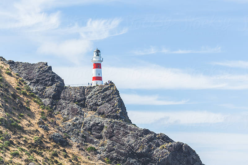 Lighthouse overlooking the rugged coast of New Zealand by Maximilian Guy McNair MacEwan for Stocksy United