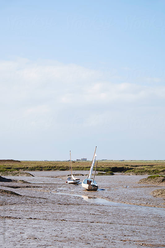 Sailing boats at low tide. Brancaster Staithe, Norfolk, UK. by Liam Grant for Stocksy United