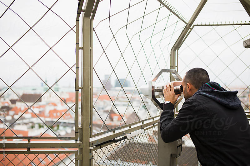 Man looking through binocular by Jovana Rikalo for Stocksy United