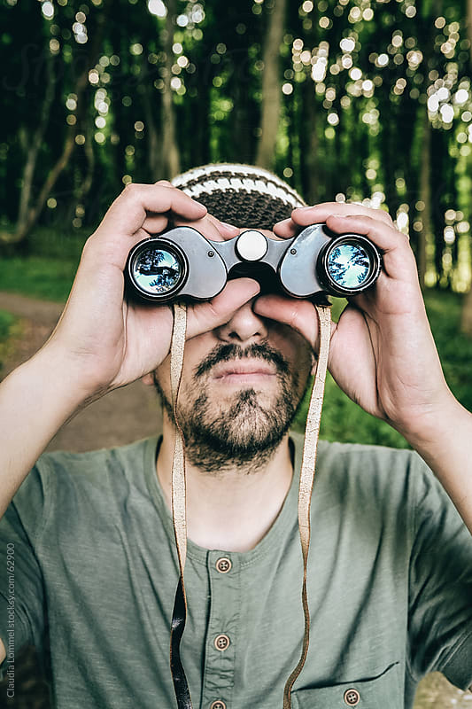 Man Looking through Old Binoculars Looking for Something in the Distance by Claudia Lommel for Stocksy United