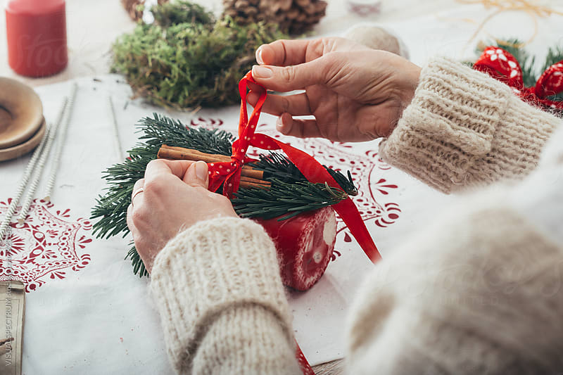 DIY Christmas - Close Up of Woman's Hand Tying Cinnamon Sticks and Fir Twigs to Big Red Candle by Julien L. Balmer for Stocksy United