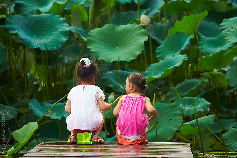 two little girls holding net by the pond side by Bo Bo for Stocksy United