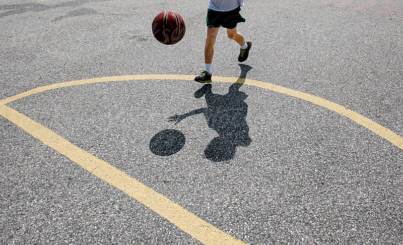 Shadow of a boy playing basketball at the playground by Cara Dolan for Stocksy United