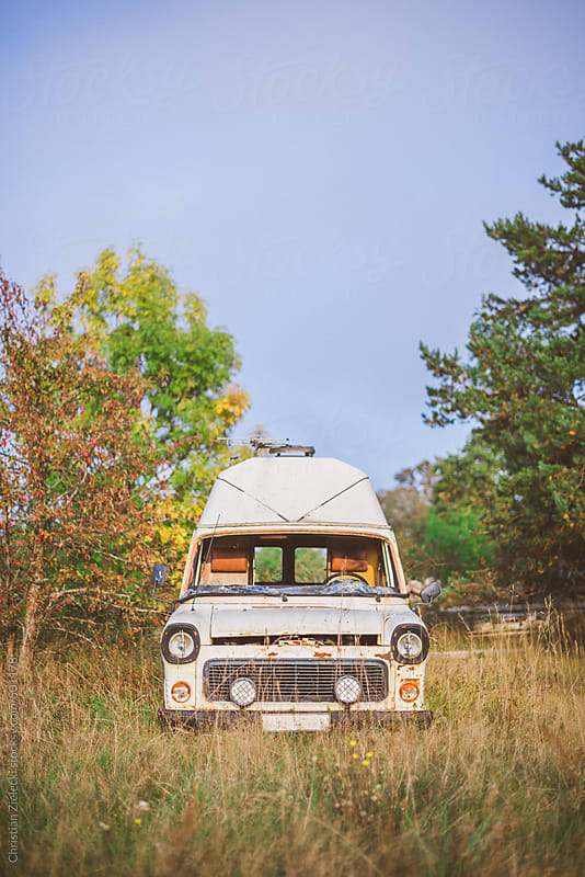 a wreck of a van on a meadow by Chris Zielecki for Stocksy United