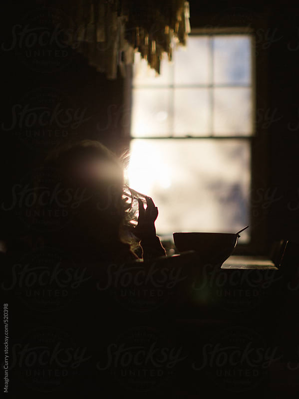 kid eating breakfast at sunrise by Meaghan Curry for Stocksy United