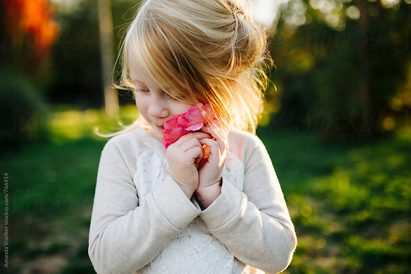 Portrait of A little girl with blonde hair feeling a rose on her cheek by Amanda Voelker for Stocksy United