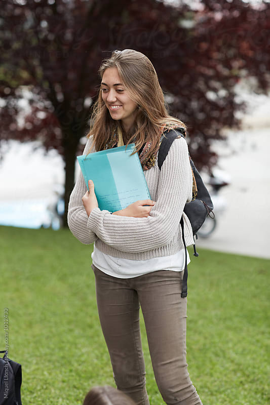 Young woman student with notebook by Miquel Llonch for Stocksy United