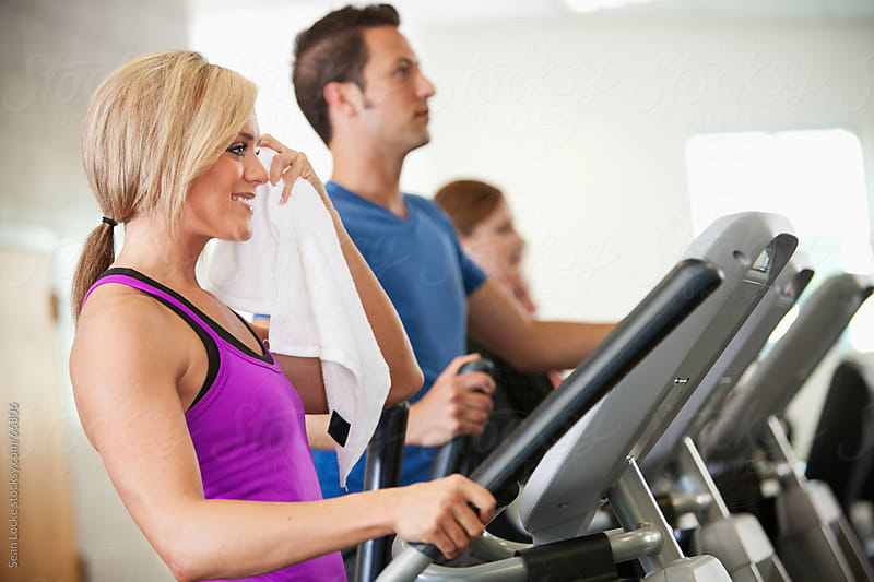 Gym: Woman Towels Off After Using Elliptical Trainer by Sean Locke for Stocksy United