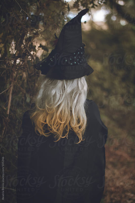 Girl wearing witch costume at Halloween in the forest by Beatrix Boros for Stocksy United