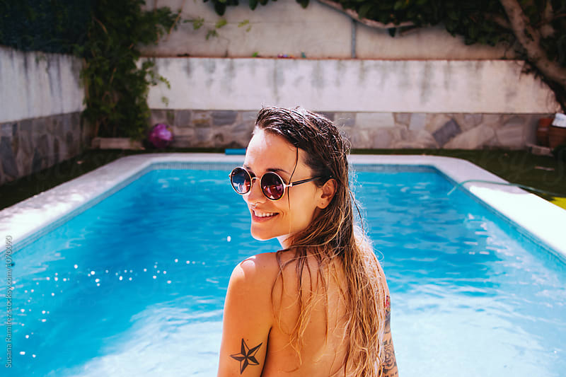 Portrait of young smiling woman in the pool by Susana Ramírez for Stocksy United