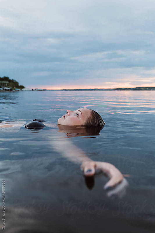 Young woman floating in calm water at sunset by Carey Shaw for Stocksy United