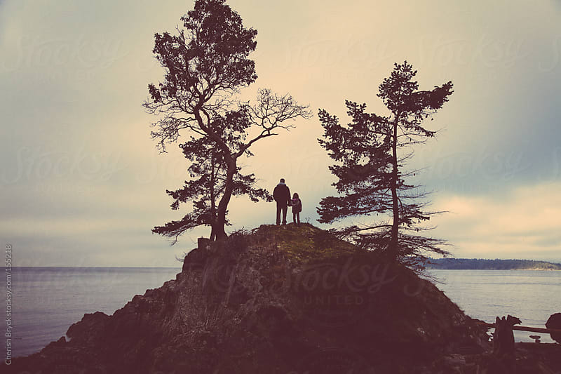 Father and daughter on a hill top at the shore. by Cherish Bryck for Stocksy United