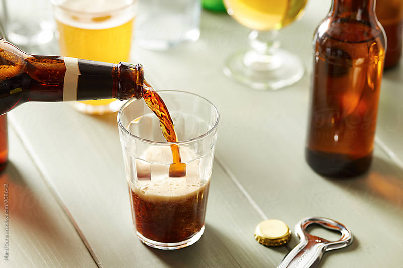 Pouring dark beer from bottle in glass by Martí Sans for Stocksy United