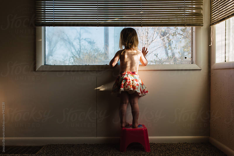 Small child looking out of window with hand up by Jessica Byrum for Stocksy United