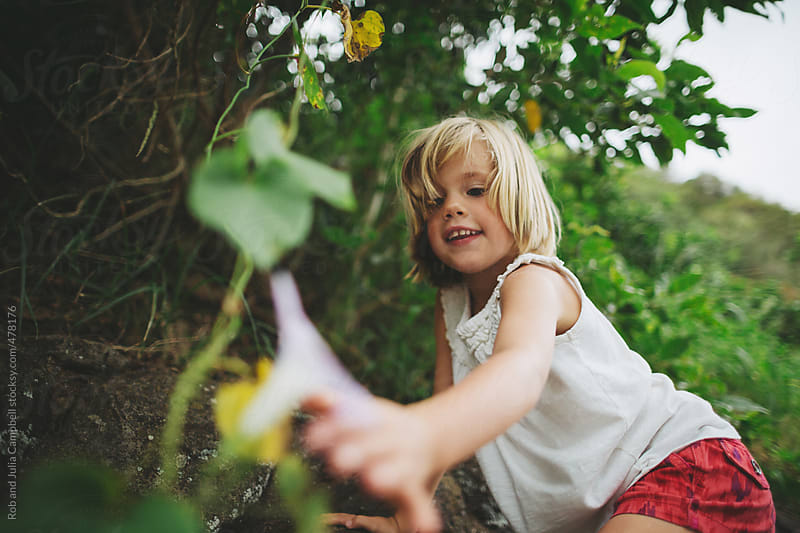 Cute young girl exploring nature in tropical area by Rob and Julia Campbell for Stocksy United