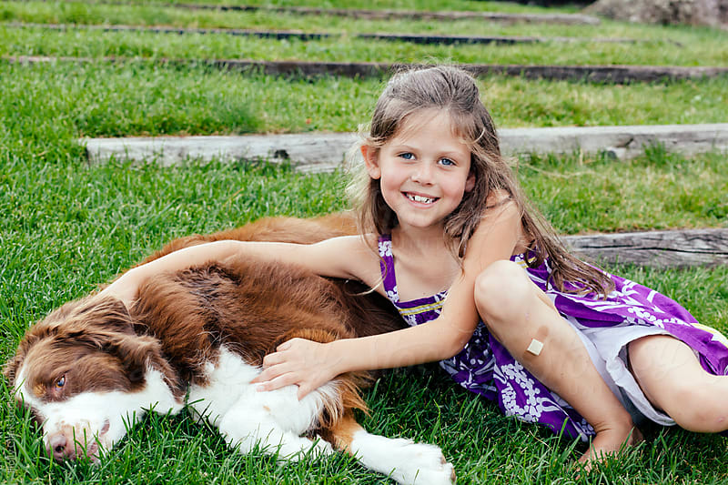 Young Girl with Dog Sitting on Grass by Holly Clark for Stocksy United
