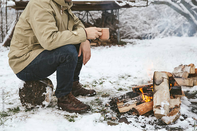 Man having hot drink next to bonfire in the snow by Lior + Lone for Stocksy United