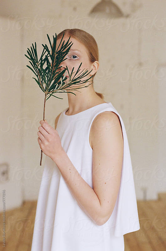 Young woman looking through green sprig by Lyuba Burakova for Stocksy United