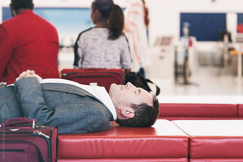 Airport: Man Takes Quick Nap In Airport Terminal  by Sean Locke for Stocksy United