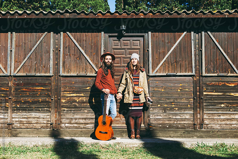 Portrait of hipster couple in front of a wooden cabin in the mountain. by BONNINSTUDIO for Stocksy United