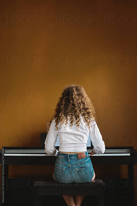 young girl playing piano by Alexander Grabchilev for Stocksy United