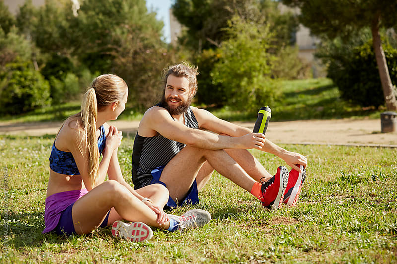Man Talking With Female Friend After Workout In Park by ALTO IMAGES for Stocksy United