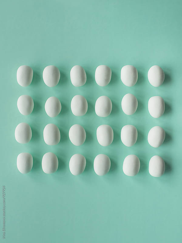 White egg shaped candies on the light turquoise background by Irina Efremova for Stocksy United