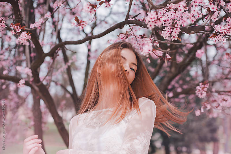 Portrait of a freckled woman in pink blossom tree by Maja Topcagic for Stocksy United
