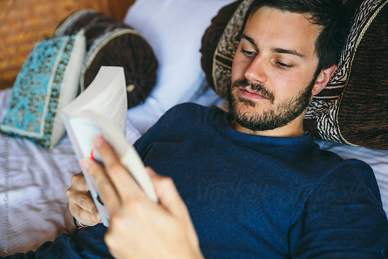 Young bearded man reading a book laying on the bed by Alejandro Moreno de Carlos for Stocksy United
