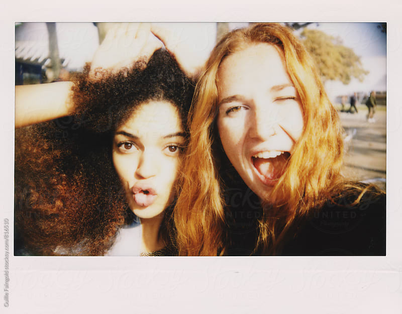 Two women taking a self-portrait with Instant camera by Guille Faingold for Stocksy United