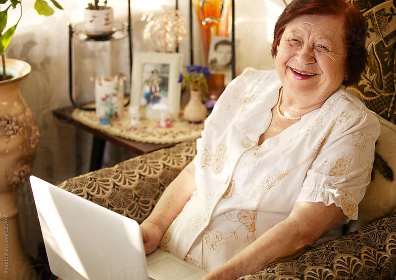 Senior woman using laptop by Ilya for Stocksy United