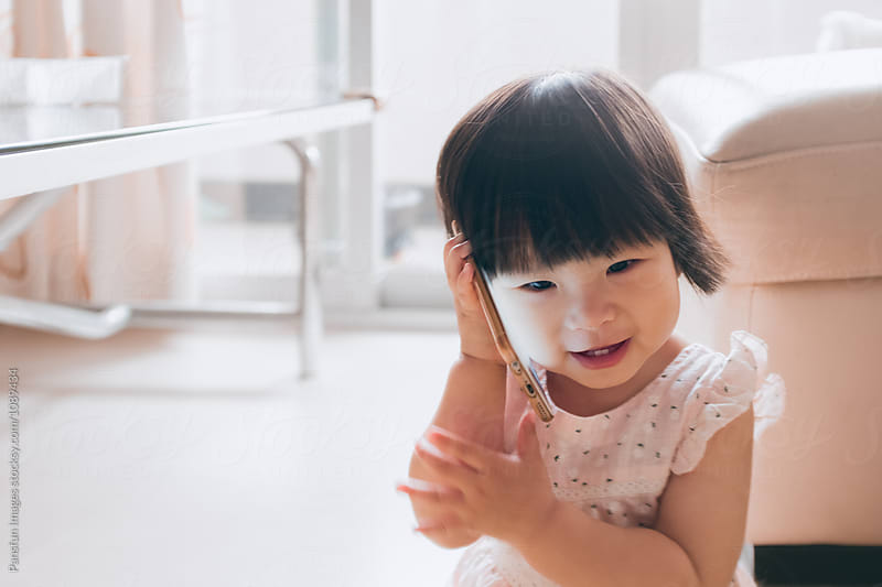 Asian baby girl with cell phone at home by Xunbin Pan for Stocksy United