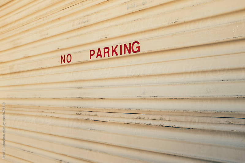 No Parking sign on garage door by Paul Edmondson for Stocksy United