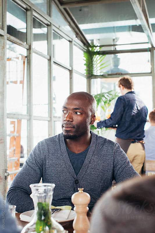 Indoor Portrait of Good-Looking Black Man Sitting in Restaurant by Julien L. Balmer for Stocksy United