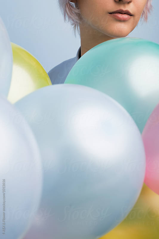 Close-up of girl's face near balloons by T-REX & Flower for Stocksy United