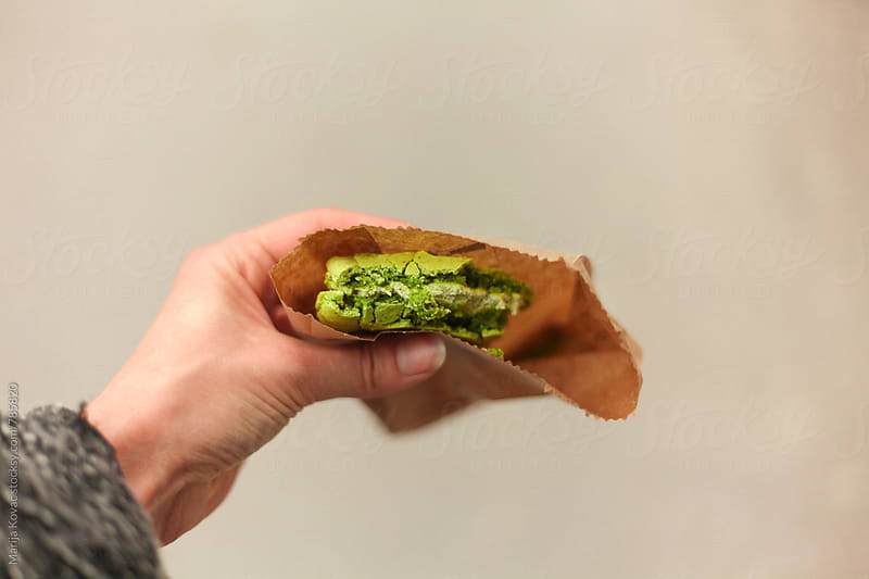 Female hand holding a green cookie - horizontal by Marija Kovac for Stocksy United