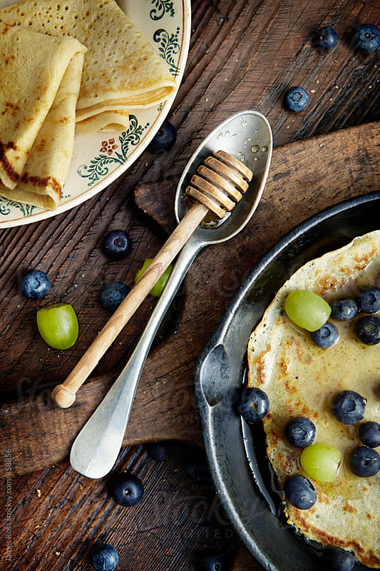 Pancakes and blueberries on a kitchen worktop by James Ross for Stocksy United